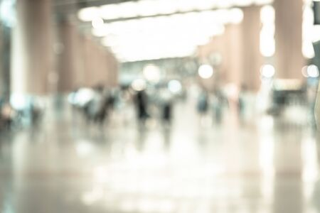Vintage toned abstract blurred passengers in an Asian airport background. Motion blur crowed of people walking along the hallway with natural light from skylight roof windows. Imagens - 137999314
