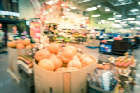 Vintage tone blurred image Halloween decoration inside grocery store in Houston, Texas, USA. Pile of pumpkins on hay, corns, garden cart wagon and scarecrow on display. Holiday festive background Stockfoto