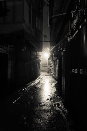 A dark, shadowy and dangerous looking urban back-alley at night time in suburbs Hanoi, Vietnam. Low light reflected on wet pavement from post lamp at the end of long road corner