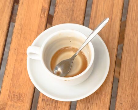 Empty cup of traditional Vietnamese milk coffee on outdoor wooden table. Popular white ceramic cup and saucer.