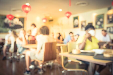 Abstract blurred background of a Chinese cafe restaurant with red lantern decoration. Diverse customers enjoying meal and beverage in warm light.