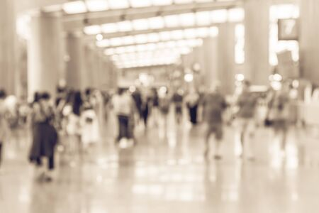 Vintage toned abstract blurred passengers in an Asian airport background. Motion blur crowed of people walking along the hallway with natural light from skylight roof windows. Imagens