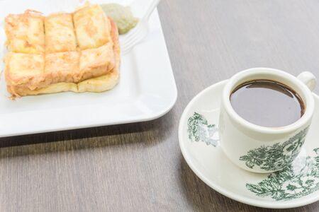 Kaya toast and kopitiam or kopi tiam style milk coffee in vintage mug. Traditional breakfast in Singapore. Factal on the cup is generic print