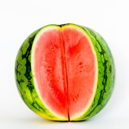 Cutout organic mini watermelon with three long slice cuts isolated on white background.