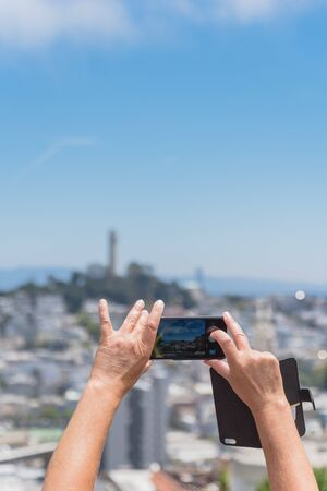 Rear view of tourist using smart phone taking photo of Coit Tower in San Francisco, California. The other hand of traveler holding the leather cell phone flip case. Imagens