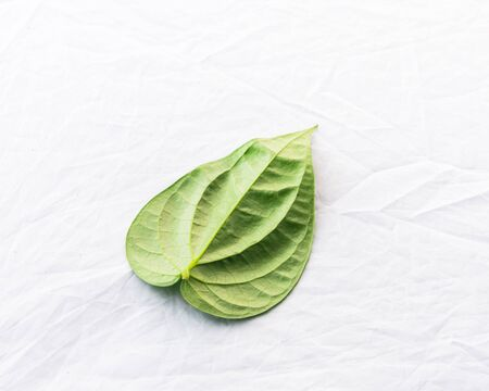 Studio shot top view one Vietnamese betel leaf paan or scientific name is Piper betle isolated on white background. A vine belonging to the Piperaceae family, mostly consumed chewing in Asia Imagens