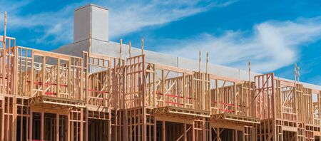 Panorama view multistory condominium under construction with wooden lumber timber framework and concrete elevator shaft. Modern apartment complex rental living space near Dallas, Texas