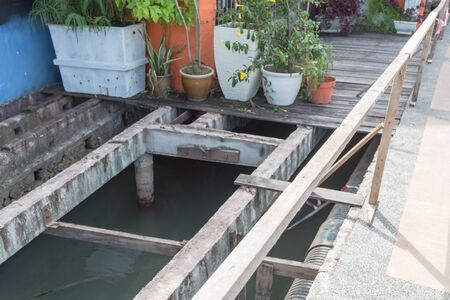 Variety of flower pots in front of residential house patio with boardwalk and under deck drainage along Malacca River, Malaysia. Remodel of deteriorated and new beams planks platform backwall 免版税图像