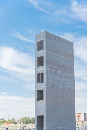 Close-up of elevator shaft for a new condominium building under construction in Richardson, Texas, America. Lookup view of concrete elevator tower under cloud blue sky