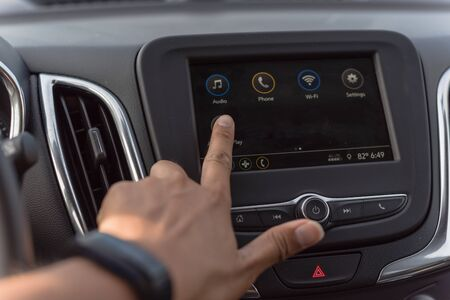 Close-up view of Asian male hand touching screen in modern car. Left hand wears a black smart watch adjust LCD dashboard system control interface on black car interior