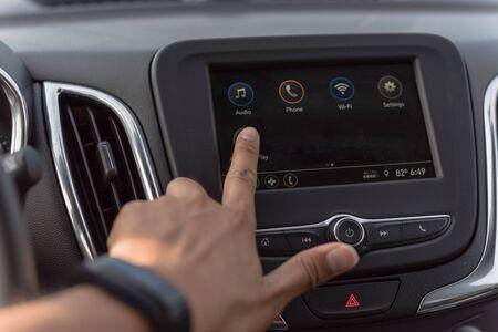 Nahaufnahme des asiatischen männlichen Handberührungsbildschirms im modernen Auto. Die linke Hand trägt eine schwarze Smartwatch, die die Steuerschnittstelle des LCD-Dashboard-Systems im schwarzen Autoinnenraum einstellt
