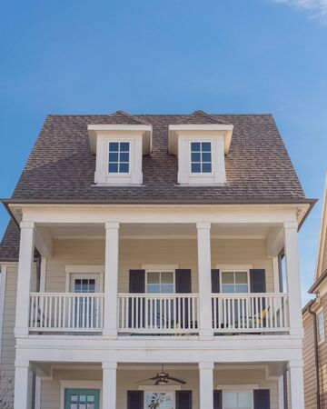 Second story porch with white painted outer edge and banister. Dormer roof windows with weathered shingle siding tiles under cloud blue sky. Country –style houses in suburbs Dallas, Texas, USA