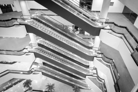 Toned photo escalator stack inside a modern office space on each floor. Typical scene at commercial building in Singapore. Banco de Imagens
