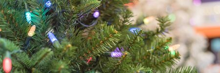 Panorama view artificial Christmas tree with pre-lit multi color lights at home improvement store in Texas, America. Close-up on pine needle with nice bokeh defocused background. Stock Photo