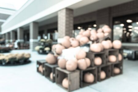 Vintage tone blurred customer shopping for Halloween supplies at grocery store in Houston, Texas. Pile of pumpkins on hay, corns, garden cart wagon and scarecrow on display. Holiday festive background
