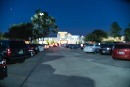 Blurred abstract retail store facade of modern shopping center in Humble, Texas, US at sunset. Mall complex with row of cars in outdoor uncovered parking lots with light poles in background