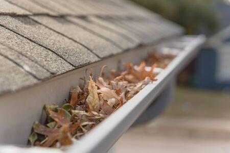 Gouttière obstruée près des bardeaux du toit d'une maison d'habitation pleine de feuilles séchées et sale à nettoyer. Tuyau de vidange bloqué sur le toit. Concept de nettoyage de gouttière et d'entretien de la maison