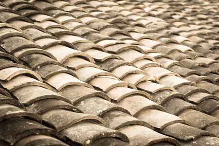 Vintage tone curved clay tiled roof in various colors from an old house in North Vietnam, late afternoon light. Ancient, weathered roofing surface, moss texture. Natural seamless pattern background Stock fotó