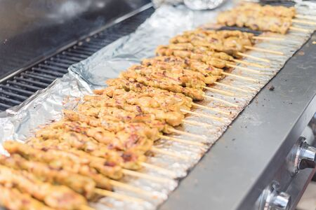 Close-up mixed Satay BBQ at Asian market in Texas, America. It is the Southeast Asian dish of seasoned, skewered and grilled meat, served with a sauce