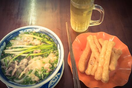 Top view bowl of fresh Vietnamese beef rice noodle soup Pho Bo served with sliced rare beef, scallions and few herbs. Side dish is Youtiao cakwe and iced tea. Popular Vietnamese breakfast set Stock Photo