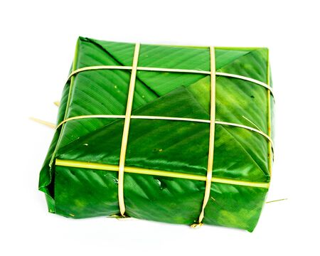 One Chung Cake isolated on white. Square glutinous sticky rice cake, stuffed with pork meat, green beans, wrapped tied in bamboo leaf and strings. Traditional Vietnamese New Year Tet food