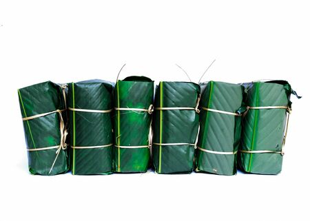 Pile of Chung Cakes isolated on white. Square glutinous sticky rice cake, stuffed with pork meat, green beans, wrapped tied in bamboo leaf and strings. Traditional Vietnamese New Year Tet food Stock fotó - 138198768