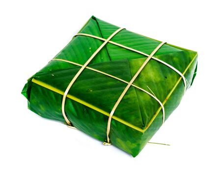 One Chung Cake isolated on white. Square glutinous sticky rice cake, stuffed with pork meat, green beans, wrapped tied in bamboo leaf and strings. Traditional Vietnamese New Year Tet food Stock fotó - 138198774