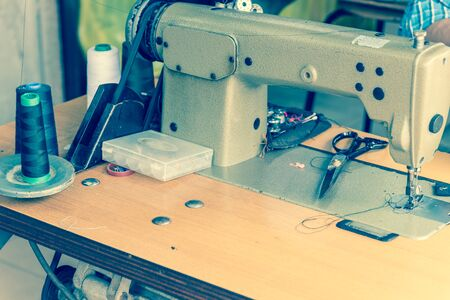 Close up view of Asian man hand with sewing machine in action. He is repairing a sewing black fabric on an old manual sewing machine at Little India, Singapore.
