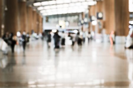 Vintage toned abstract blurred passengers in an Asian airport background. Motion blur crowed of people walking along the hallway with natural light from skylight roof windows. 版權商用圖片