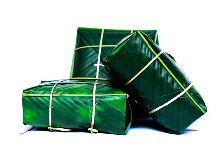 Three Chung Cakes isolated on white. Square glutinous sticky rice cake, stuffed with pork meat, green beans, wrapped tied in bamboo leaf and strings. Traditional Vietnamese New Year Tet food Stock fotó - 138199031