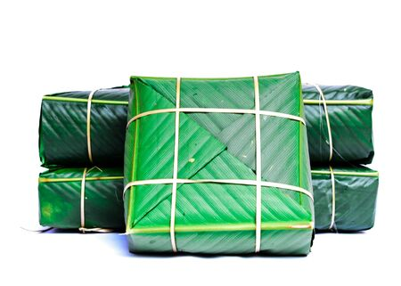 Pile of Chung Cakes isolated on white. Square glutinous sticky rice cake, stuffed with pork meat, green beans, wrapped tied in bamboo leaf and strings. Traditional Vietnamese New Year Tet food Stock fotó - 138198672