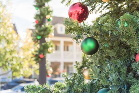 Beautiful Christmas ball hanging on pine branches at daytime light with two-story residential house in background. Baubles and spruce tree. Traditional artificial Xmas ornament near Dallas, Texas