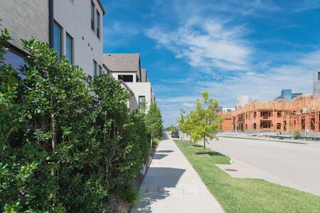 Brand new development community in North Dallas, Texas, USA with mixed of single family detached residential houses and upscale multistory apartment building complex under construction, clean sidewalk Stockfoto