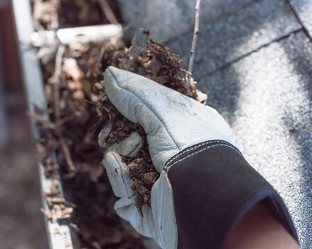 Top view man hand in gloves cleaning house gutter from leaves and dirt. Roof gutter cleaning near shingles roof in summer time Stockfoto