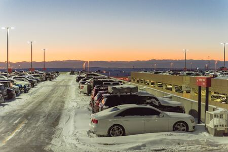 Full terminal parking at Denver International Airport (DIA) in frosty cold autumn sunset. Row of cars at busy parking lot with snowdrifts during severe weather condition in Colorado, USA.