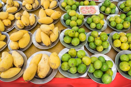Pre-pack slices cut sample of red guava and mixed, assorted fresh fruit on aluminium trays at Little India. Bunch of ripe Mango, whole guava at farmer market in Singapore.
