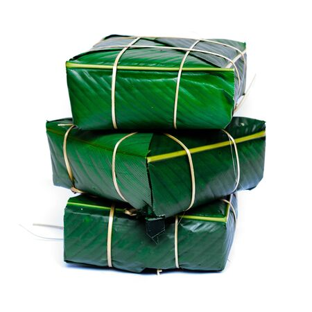 Three Chung Cakes isolated on white. Square glutinous sticky rice cake, stuffed with pork meat, green beans, wrapped tied in bamboo leaf and strings. Traditional Vietnamese New Year Tet food Stock fotó - 138198775
