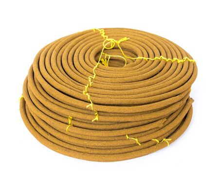 Stack of round incense or citronella spiral coils made from agarwood isolated on white background. Long lasting fragrance with woody scent for meditation, worship concept
