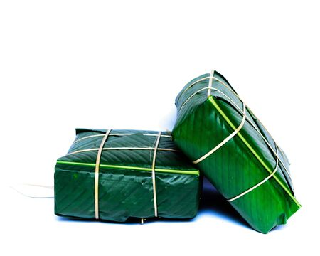 Two Chung Cakes isolated on white. Square glutinous sticky rice cake, stuffed with pork meat, green beans, wrapped tied in bamboo leaf and strings. Traditional Vietnamese New Year Tet food