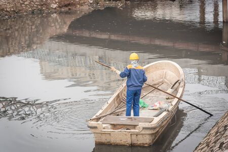 Rear view female worker cleaning a polluted canal full of dark water and variety of wastes in Hanoi. Pollution is one of the most serious problems of Vietnam. Crew in face mask and helmet Stockfoto