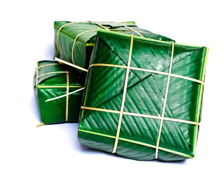 Three Chung Cakes isolated on white. Square glutinous sticky rice cake, stuffed with pork meat, green beans, wrapped tied in bamboo leaf and strings. Traditional Vietnamese New Year Tet food Stock fotó - 138199224
