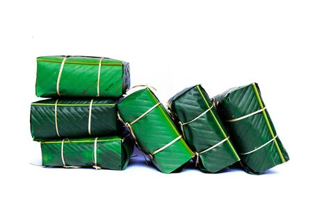 Pile of Chung Cakes isolated on white. Square glutinous sticky rice cake, stuffed with pork meat, green beans, wrapped tied in bamboo leaf and strings. Traditional Vietnamese New Year Tet food