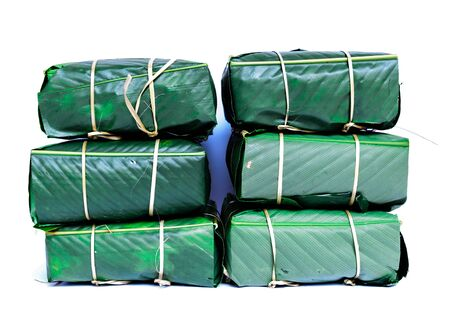 Stack of Chung Cakes isolated on white. Square glutinous sticky rice cake, stuffed with pork meat, green beans, wrapped tied in bamboo leaf and strings. Traditional Vietnamese New Year Tet food