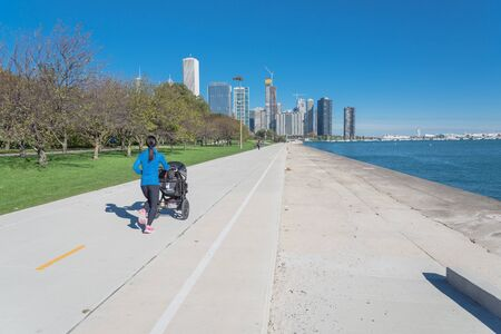 Rear view of fit Asian lady running and pushing stroller along shoreline of Michigan Lake with downtown Chicago skylines in background. Fit sportswear woman exercise outdoor at fall daytime