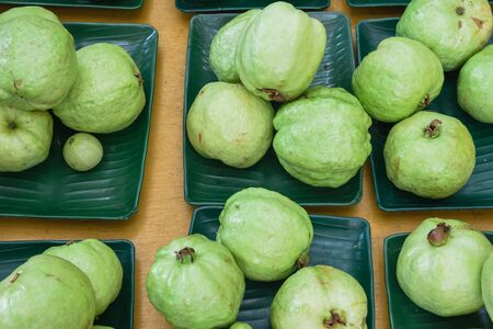 Green fresh raw whole guavas on plastic trays display at local fruit stand in Little India. Organic and healthy tropical food at Singapore farmer market.