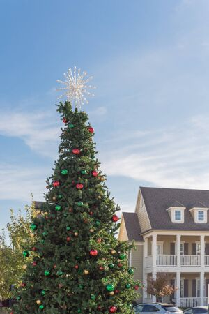 Huge Christmas tree with snowflake tree topper and colorful glass ornaments balls on display at City Square in Coppell, Texas, USA. Christmas decoration row of country-style houses near Dallas