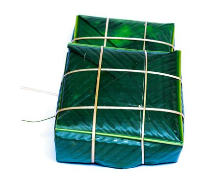 Two Chung Cakes isolated on white. Square glutinous sticky rice cake, stuffed with pork meat, green beans, wrapped tied in bamboo leaf and strings. Traditional Vietnamese New Year Tet food Stok Fotoğraf