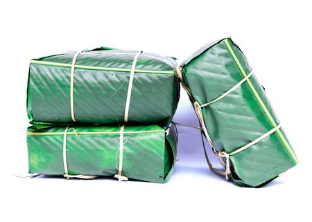 Three Chung Cakes isolated on white. Square glutinous sticky rice cake, stuffed with pork meat, green beans, wrapped tied in bamboo leaf and strings. Traditional Vietnamese New Year Tet food Stock fotó - 138198654