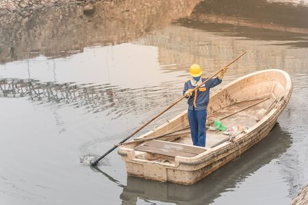 Unidentified female worker cleaning a polluted canal full of dark water and variety of wastes in Hanoi. Pollution is one of the most serious problems of Vietnam. Crew in face mask and helmet Stockfoto