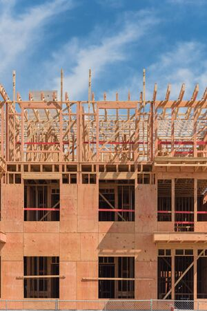 Close-up wooden framing of modern condominium building under construction in North Dallas, Texas, America. Unfinished multistory apartment complex truss, joist, beam close-up under cloud blue sky Stockfoto